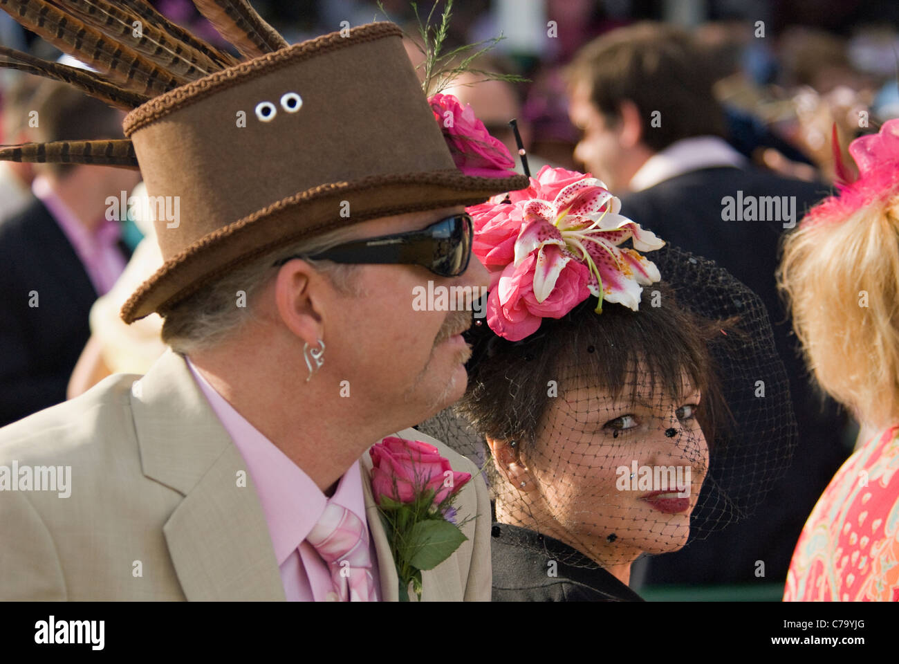 Man and Woman in Fancy Hats at Churchill Downs on Oaks Day in Louisville, Kentucky - Stock Image