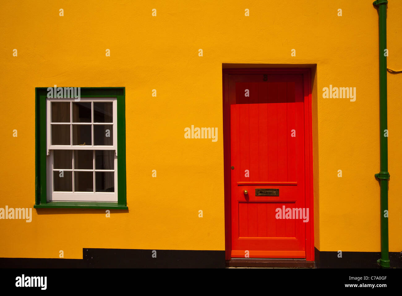 The front of a terraced house with a red door and green windows in Lyme Regis in Dorset Stock Photo