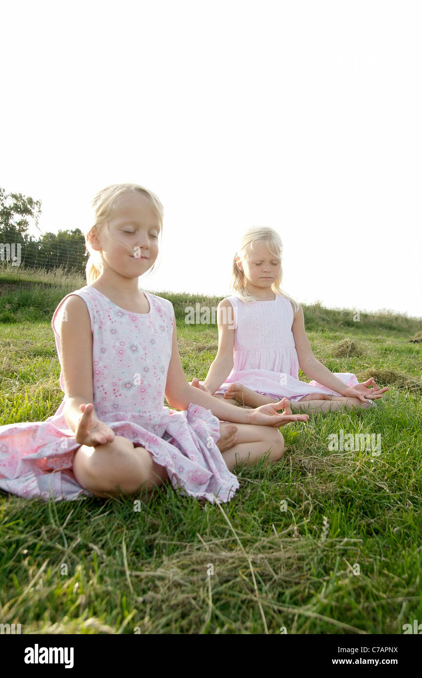 Portrait of two girl friends practicing yoga in summer, Eyendorf, Lower Saxony, Germany, Europe - Stock Image