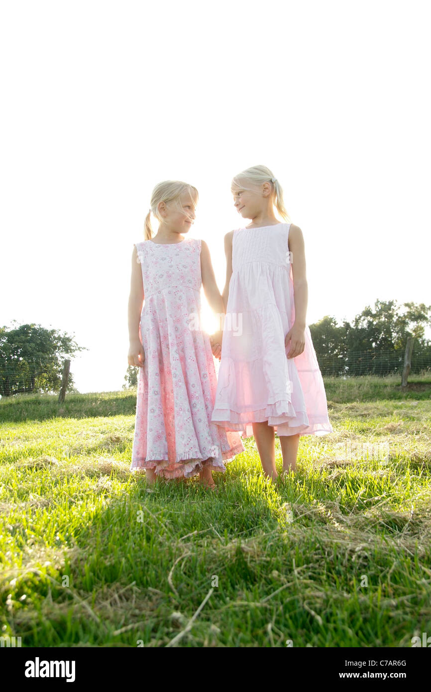 Portrait of two girl friends holding hands in summer, Eyendorf, Lower Saxony, Germany, Europe - Stock Image