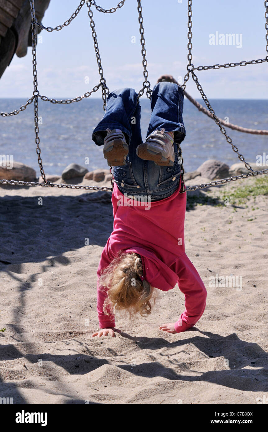 Small 6-year-old blonde girl on a playground in Westerland, Sylt Island, Germany, Europe - Stock Image