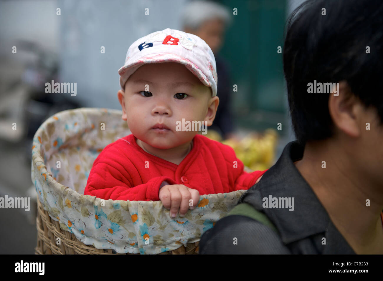 Chinese migrant woman carrying a baby on her back with a bamboo basket in Beijing, China.16-Sep-2011 - Stock Image