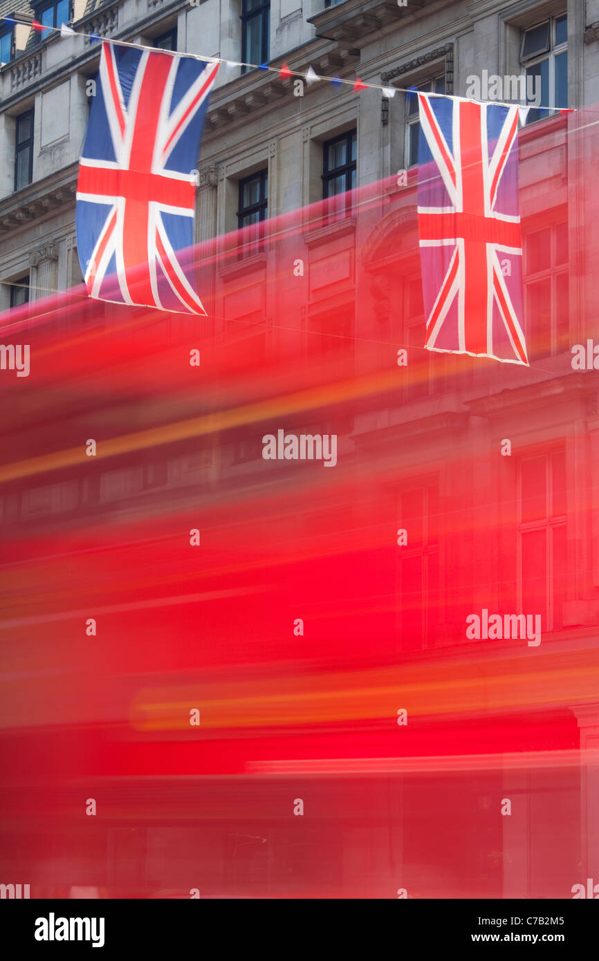 Red bus and Union Jack Flags Regent Street London - Stock Image