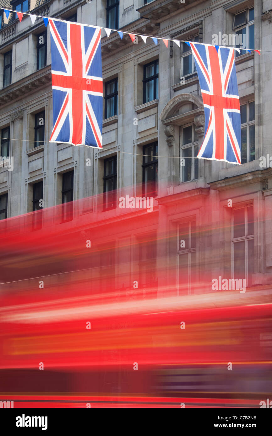 Red bus and Union Jack Flags on Regent Street; London; England - Stock Image