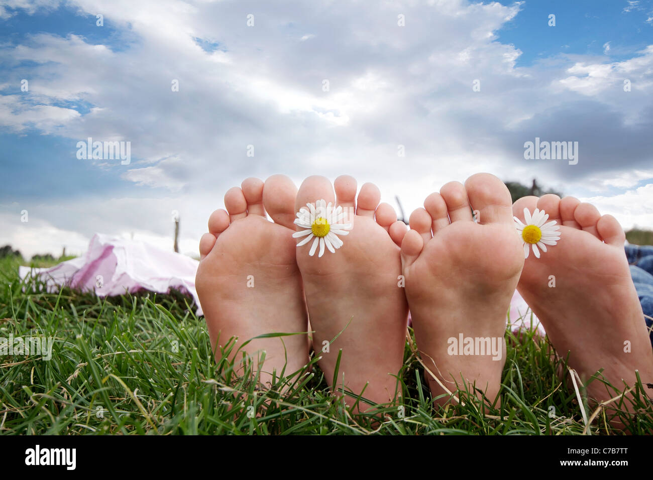 Children playing and relaxing on a meadow in summer, barefoot, Eyendorf, Lower Saxony, Germany, Europe - Stock Image