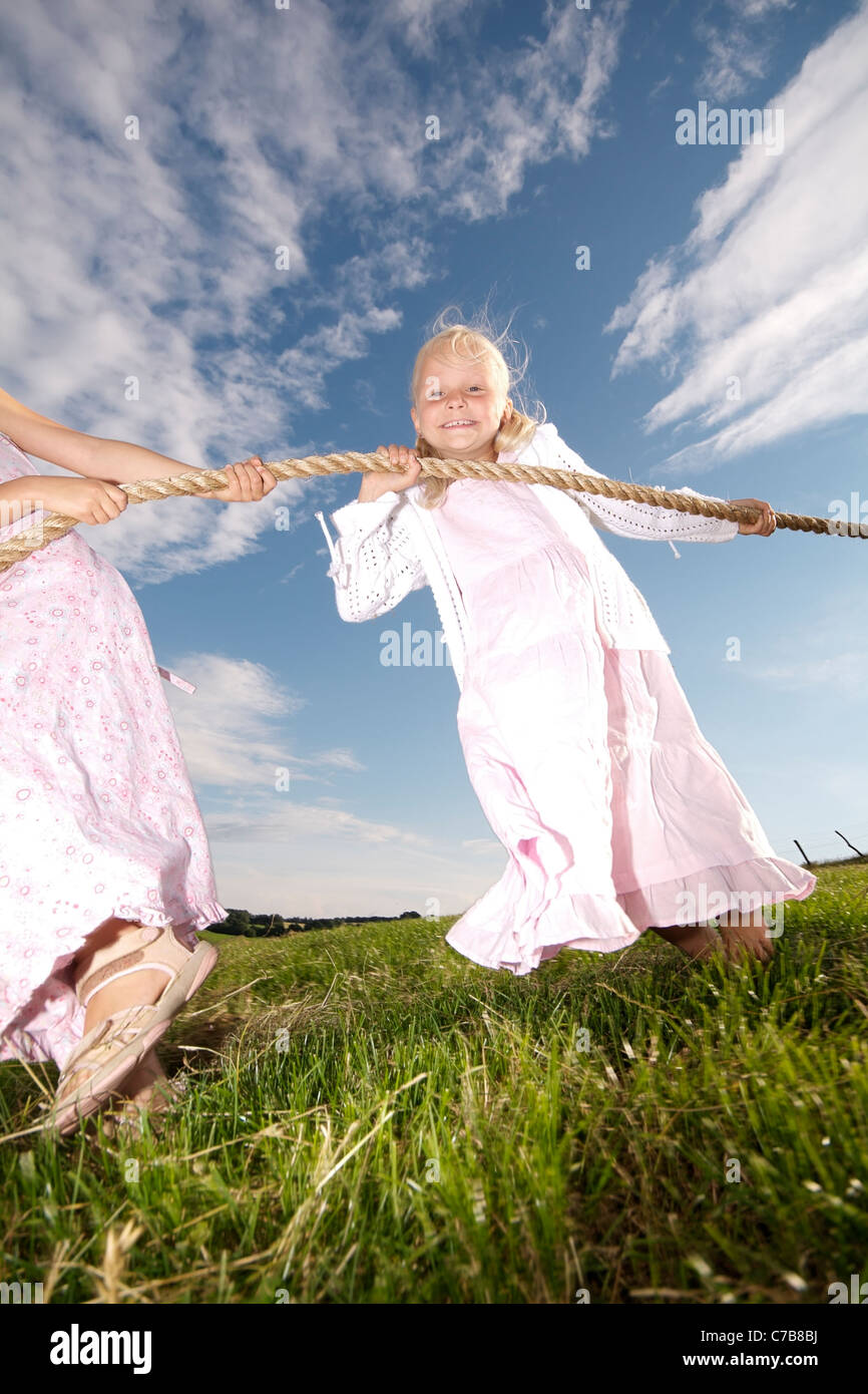 Children playing tug-of-war on a meadow in summer, Eyendorf, Lower Saxony, Germany, Europe - Stock Image