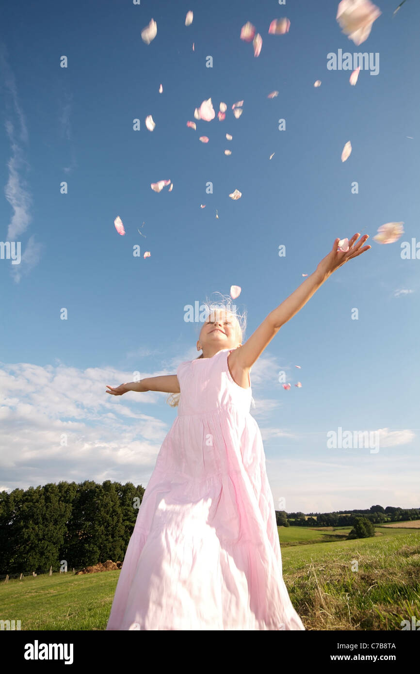 Girl scattering petals in the air in summer, Eyendorf, Lower Saxony, Germany, Europe - Stock Image