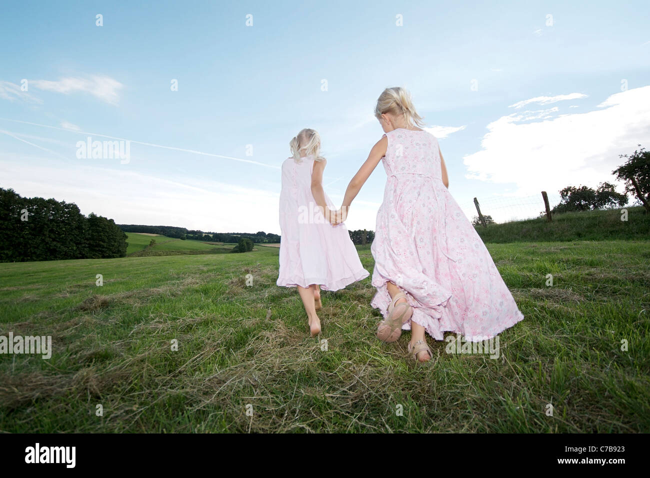 Girls running across a meadow in summer, Eyendorf, Lower Saxony, Germany, Europe - Stock Image