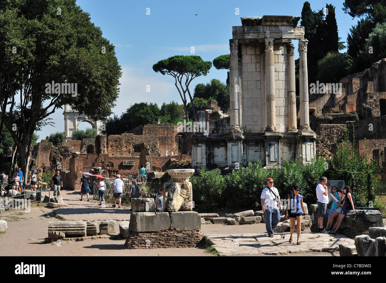 Rome. Italy. Tourists wander amongst the ruins of the Roman Forum (Foro Romano) . The remains of the Temple of Vesta - Stock Image