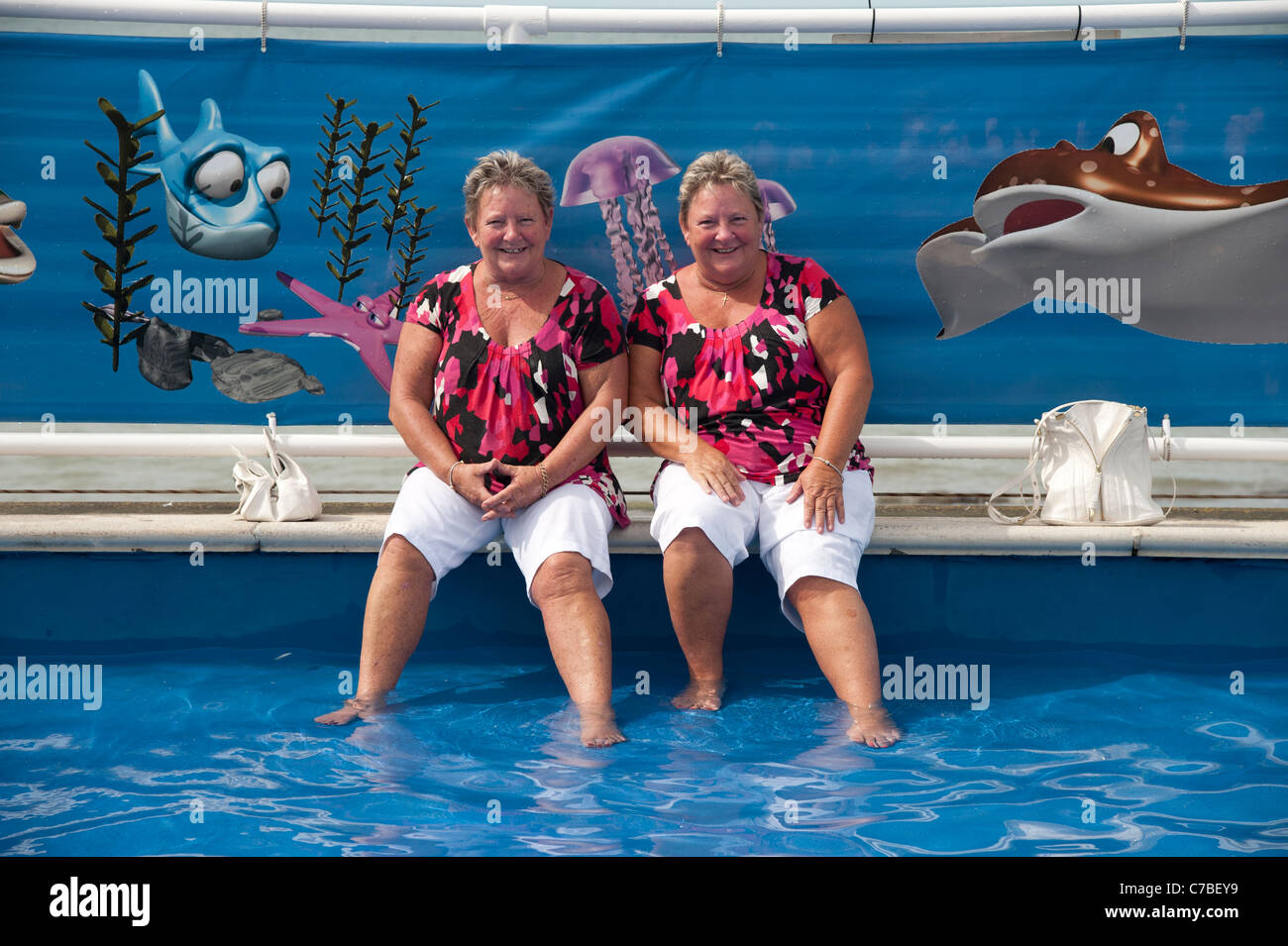 Two middle aged identical twin sisters wearing matching clothes in the paddling pool, Aberystwyth Wales UK, summer - Stock Image