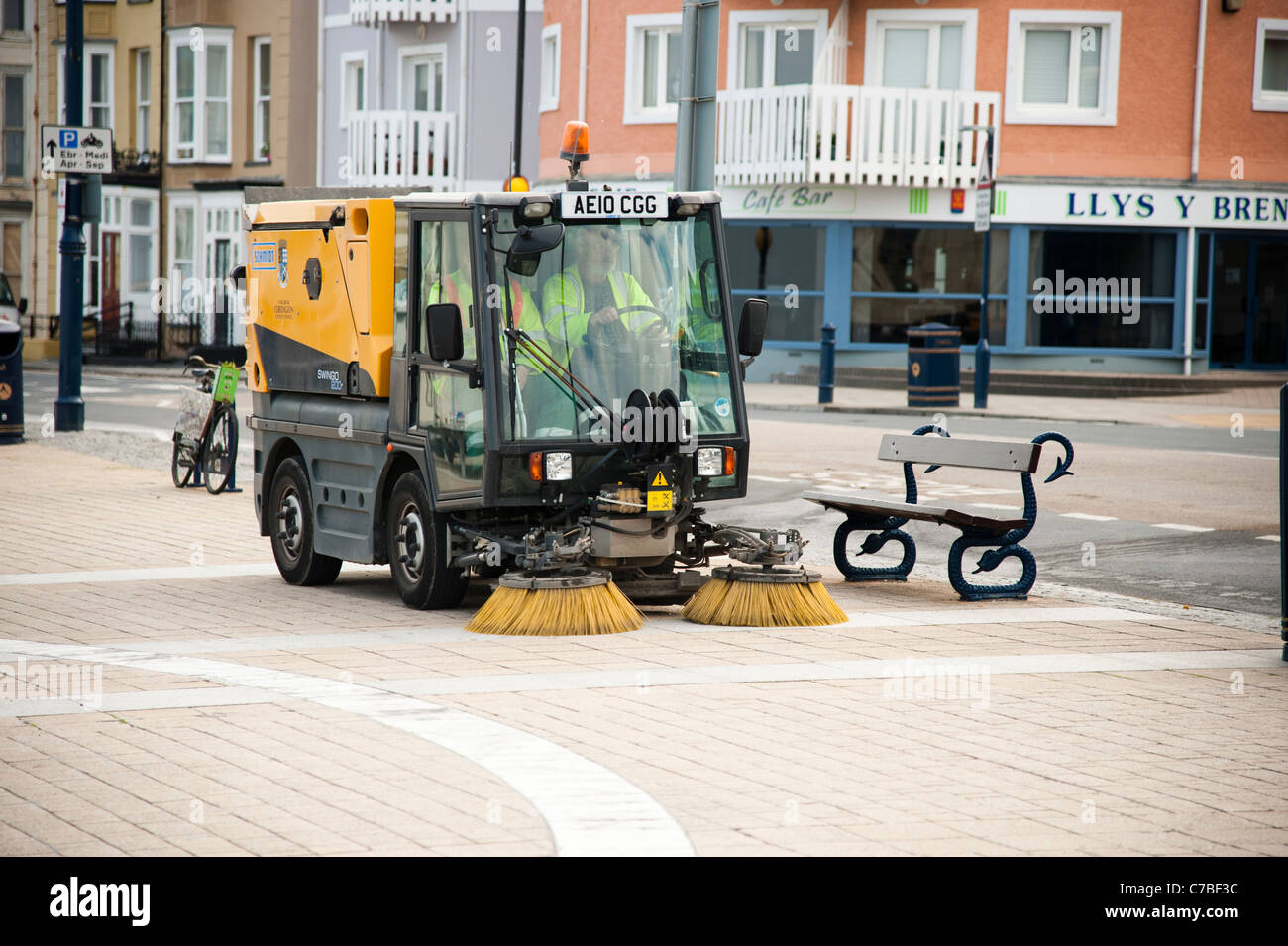 a small compact Schmidt Swingo 200 roadsweeper cleaning the pavement on Aberystwyth promenade UK - Stock Image