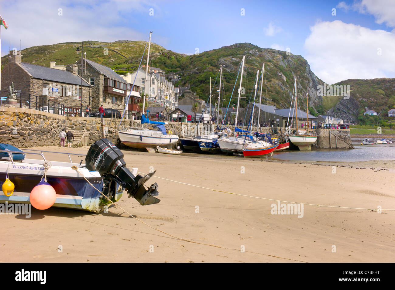 Low tide at Barmouth harour, colorful yachts roped to harbour wall, tourists, old buildings and rocky hillside in - Stock Image