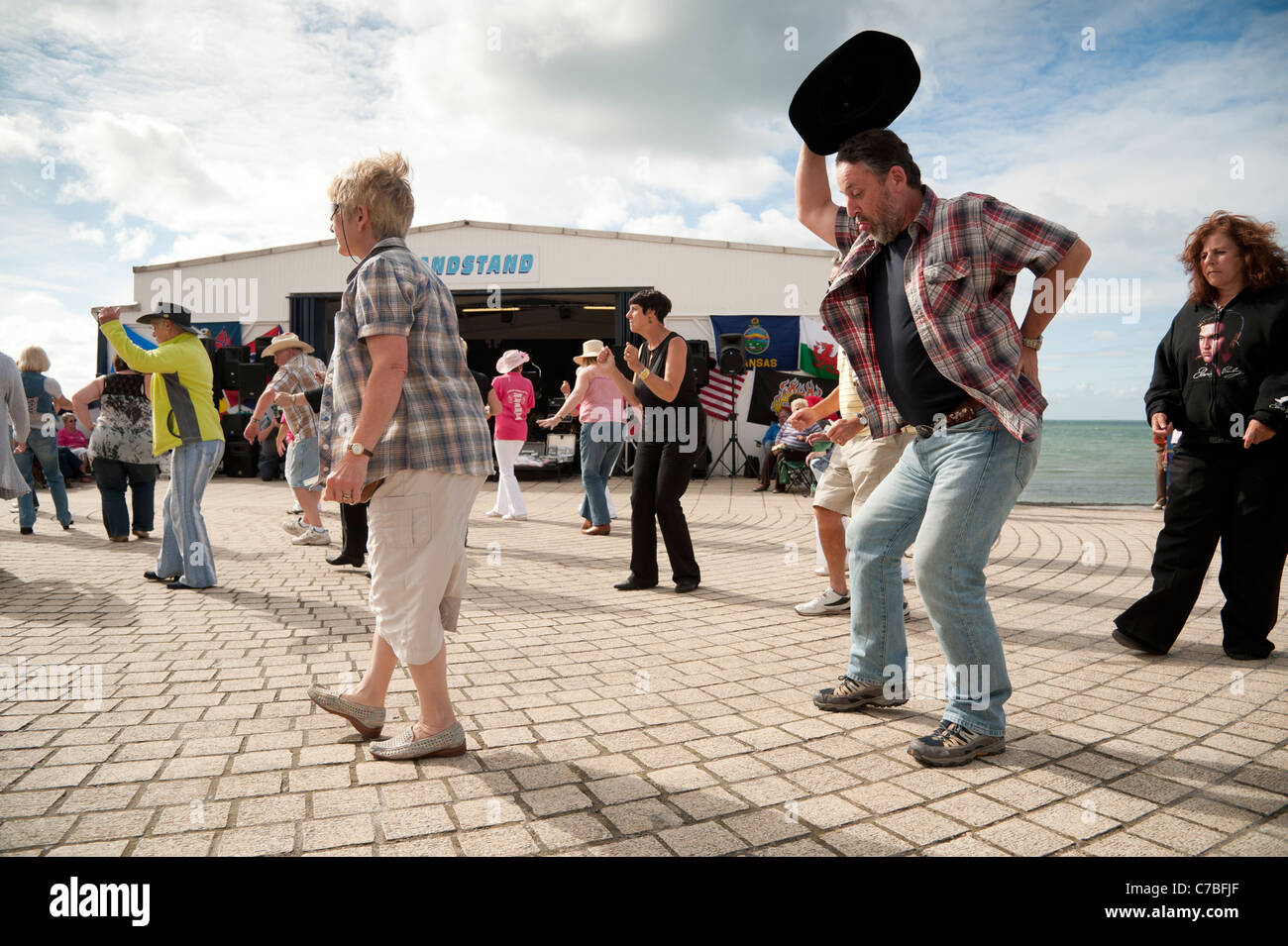 People Line dancing in aid of charity on Aberystwyth promenade wales UK - Stock Image