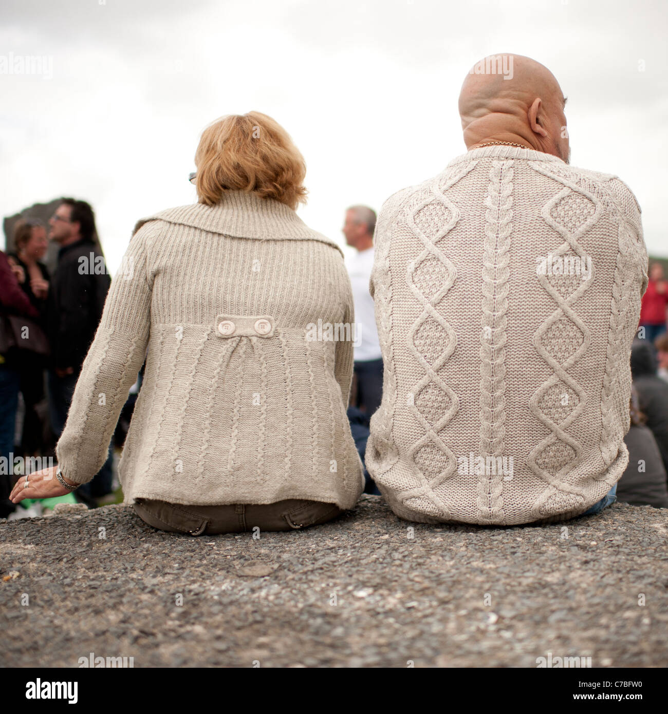 Rear views of a man and woman wearing matching beige cardigans - Stock Image