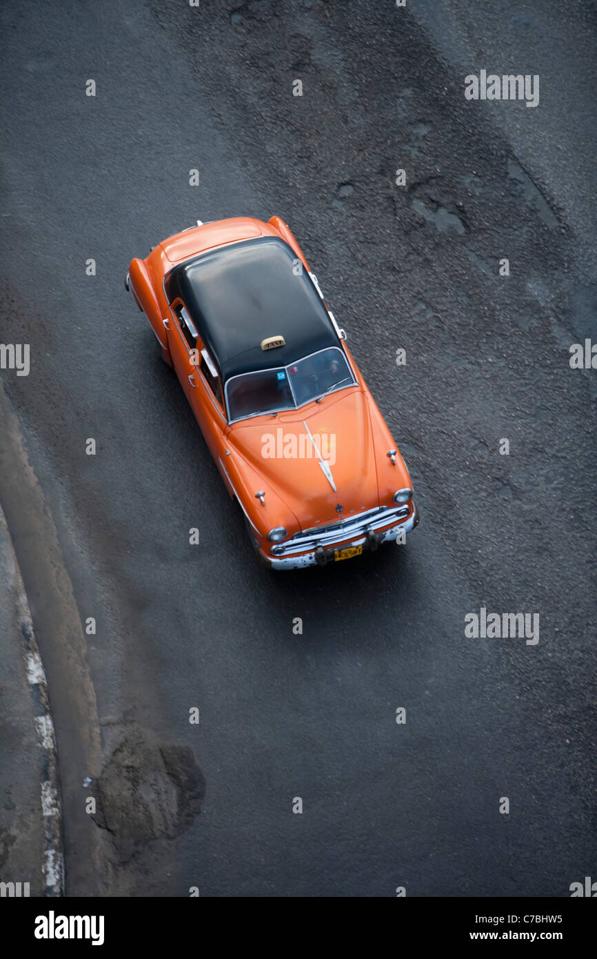 Orange vintage American car taxi on Malecon sea wall, City of Havana, Havana, Cuba - Stock Image
