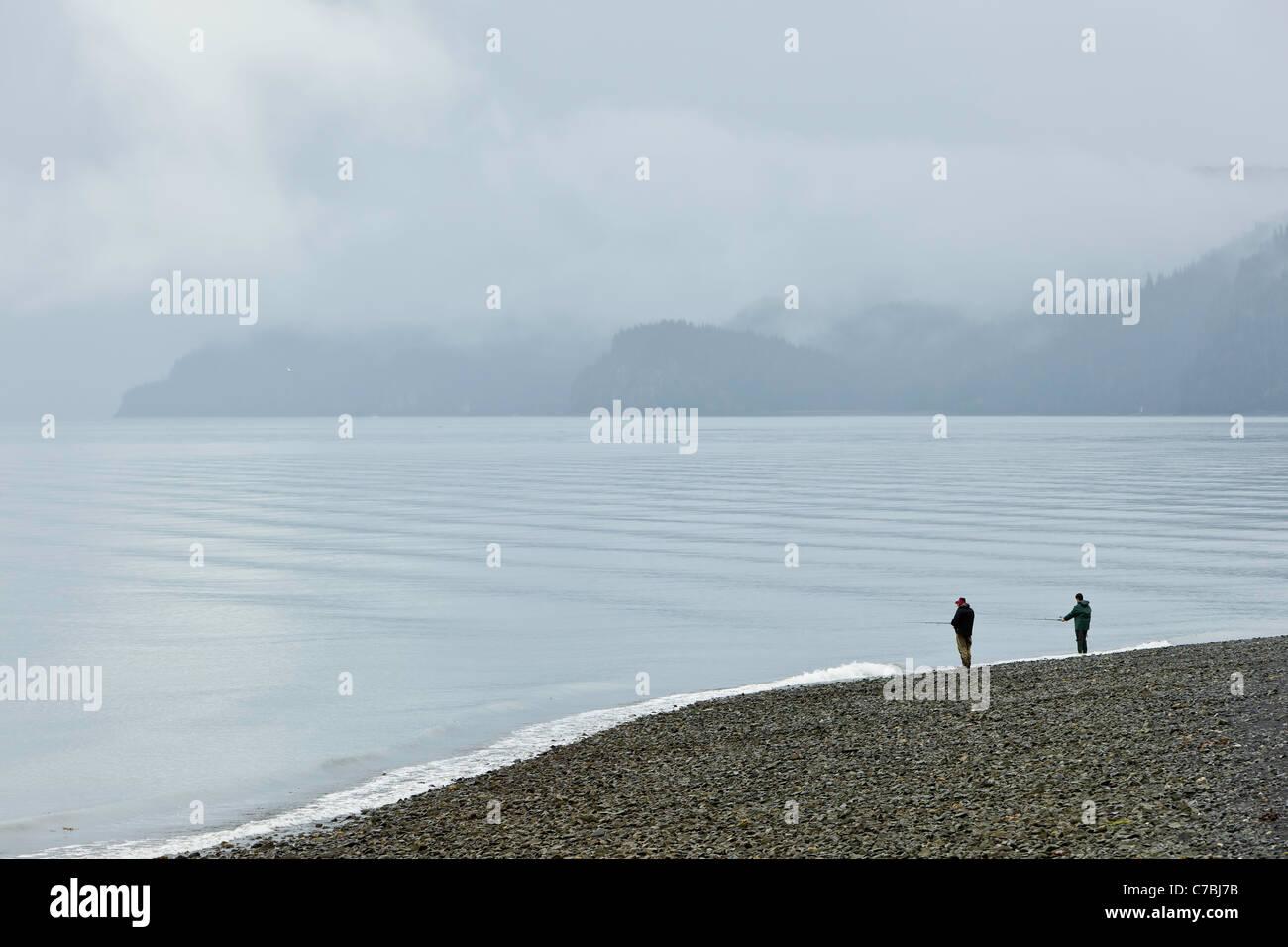 Two fishermen fishing for salmon in Resurrection Bay along Lowell Point in morning fog in Seward, Alaska. - Stock Image
