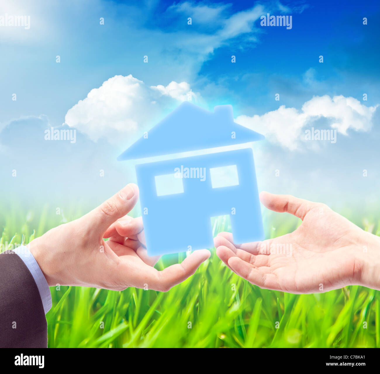 The House in the Hand against the sunny blue sky as a symbol of the real estate business. - Stock Image