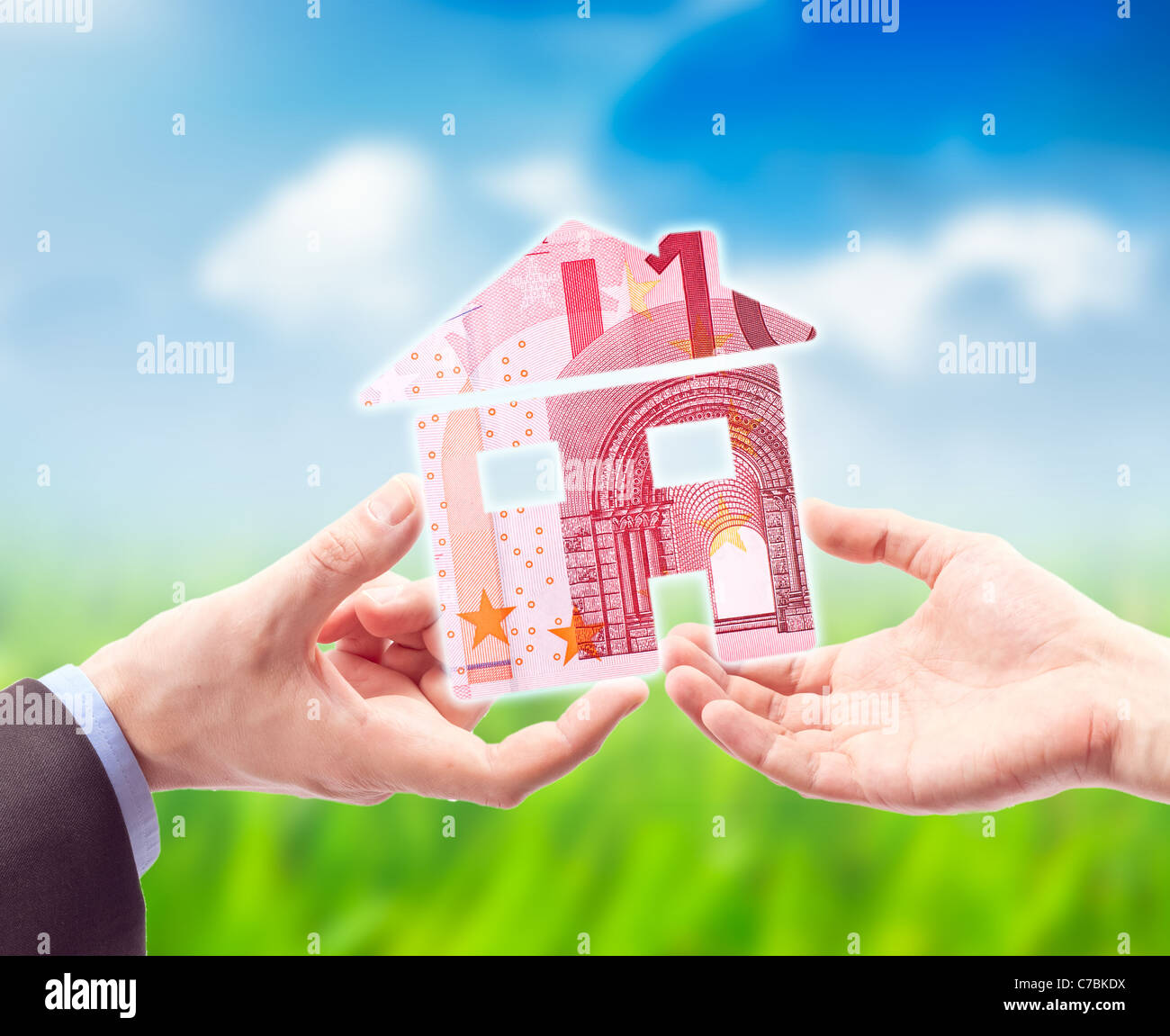 The House made from EURO in the Hand against the sunny blue sky as a symbol of the real estate business - Stock Image