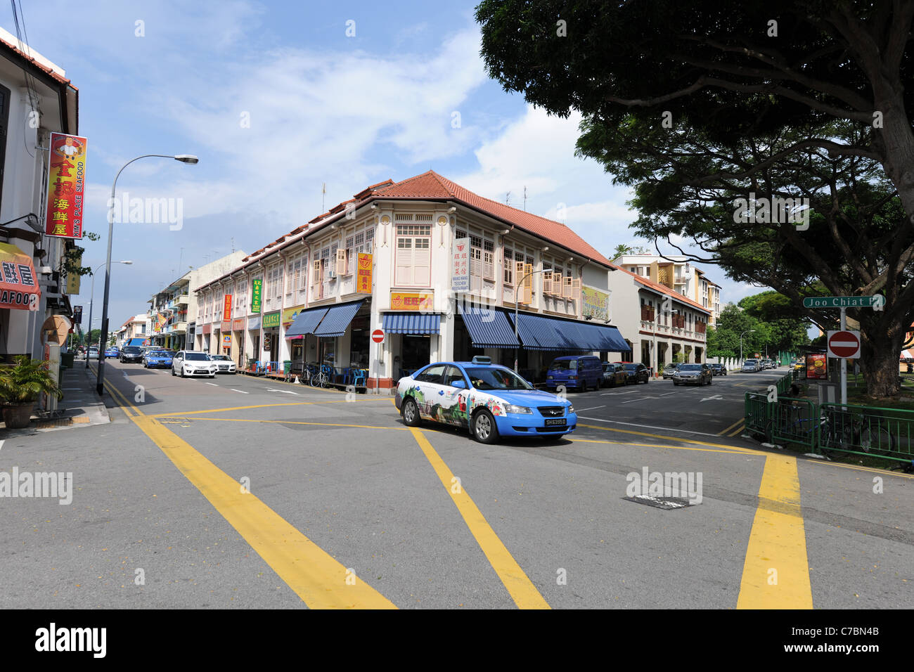 taxi, road junction and shophouses in the residential  conservation area Joo Chiat, Singapore - Stock Image