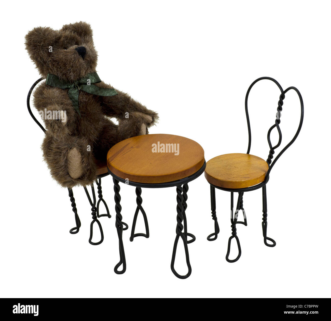 Teddy Bear Sitting At A Bistro Setting With A Table And A Set Of Chairs For