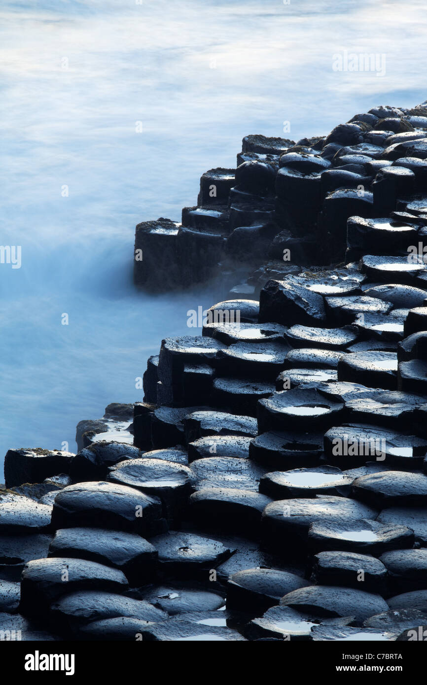 Waves splashing over basalt columns near sunset, Giant's Causeway, County Antrim, Northern Ireland, United Kingdon - Stock Image
