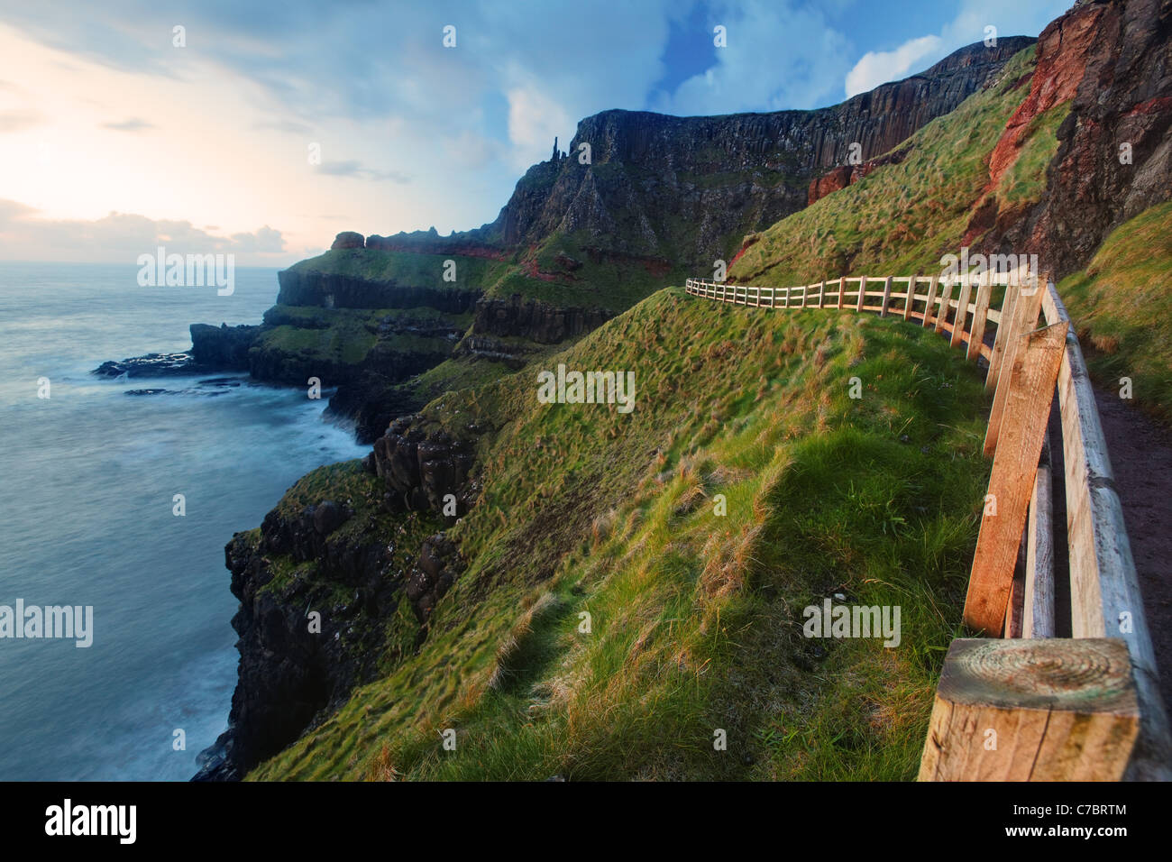 Fenced cliffside trail on Benbane Head near sunset, Giant's Causeway, County Antrim, Northern Ireland, United - Stock Image