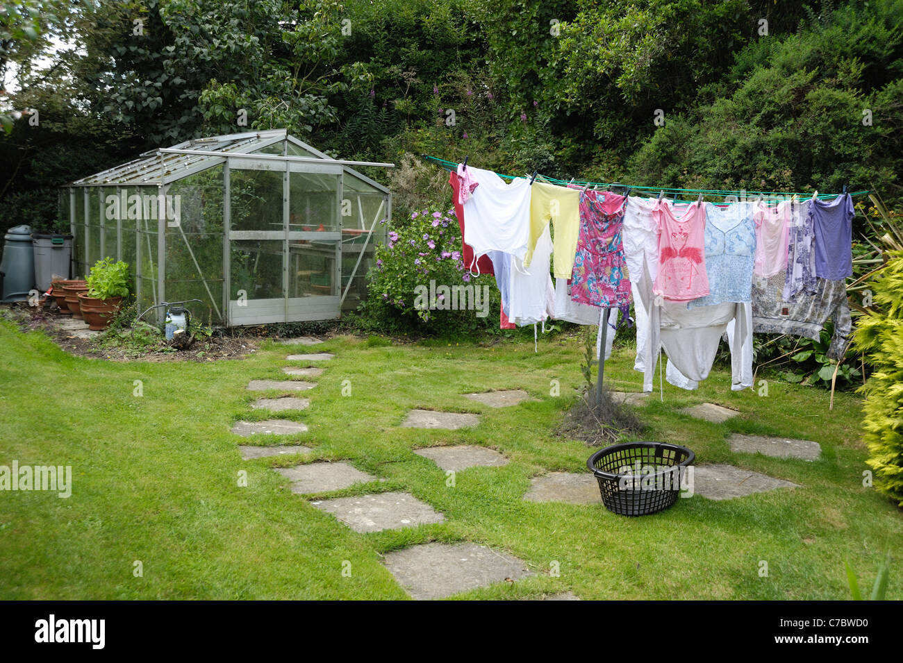 Garden greenhouse, small lawn paving and washing line with washing - Stock Image