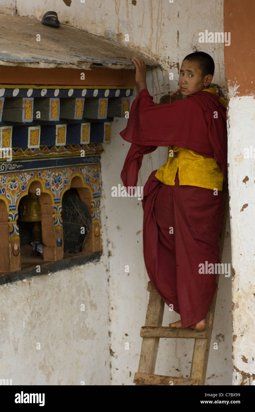 His fellow apprentice monks have thrown this boy's sandal onto the roof of a bank of prayer wheels at their - Stock Image