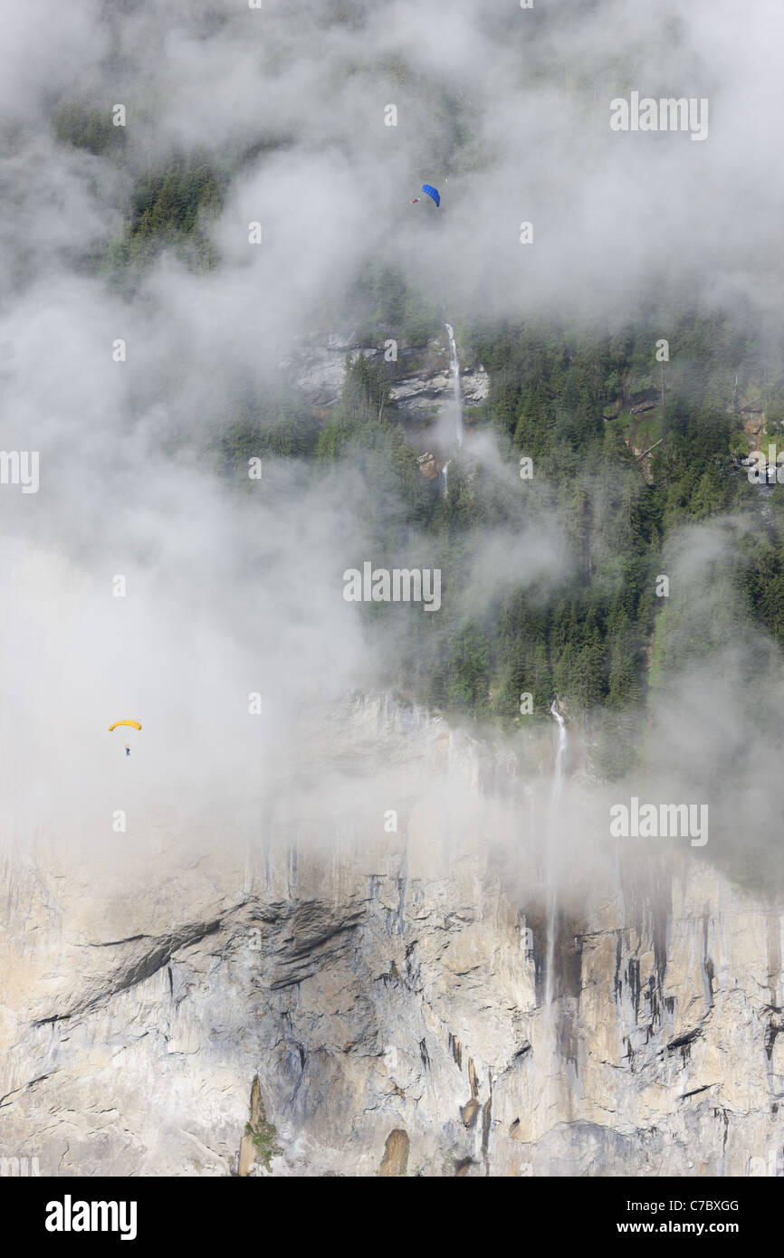TWO SKYDIVERS / PARACHUTISTS are soaring by the magnificient Staubbachfall waterfall above the Lauterbrunnen Valley. - Stock Image