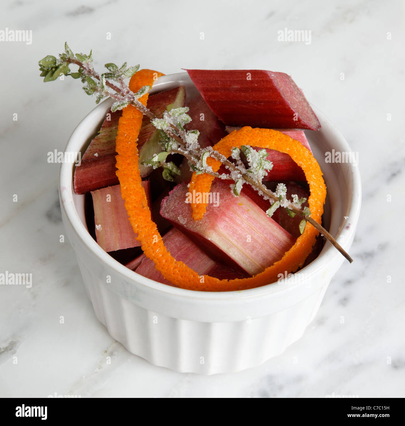 Chopped rhubarb in bowl garnished with orange peel and lavender sprig, by pastry chef Laurie Pfalzer, Pastry Craft - Stock Image
