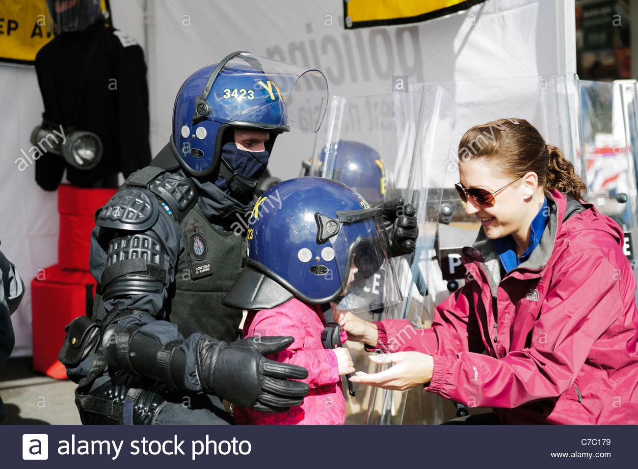 Riot police man letting a toddler try on a helmet at open day, Hereford Police station, England, UK. Mother & - Stock Image