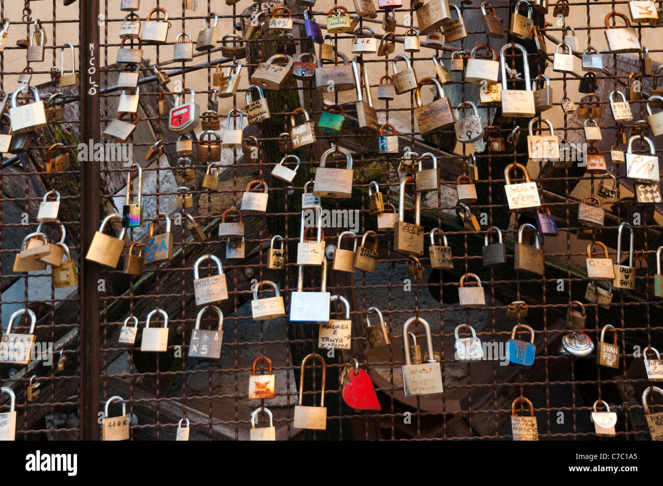 Pad locks attached to a metal grid display messages of everlasting love and commitment, Borghetto Italy - Stock Image