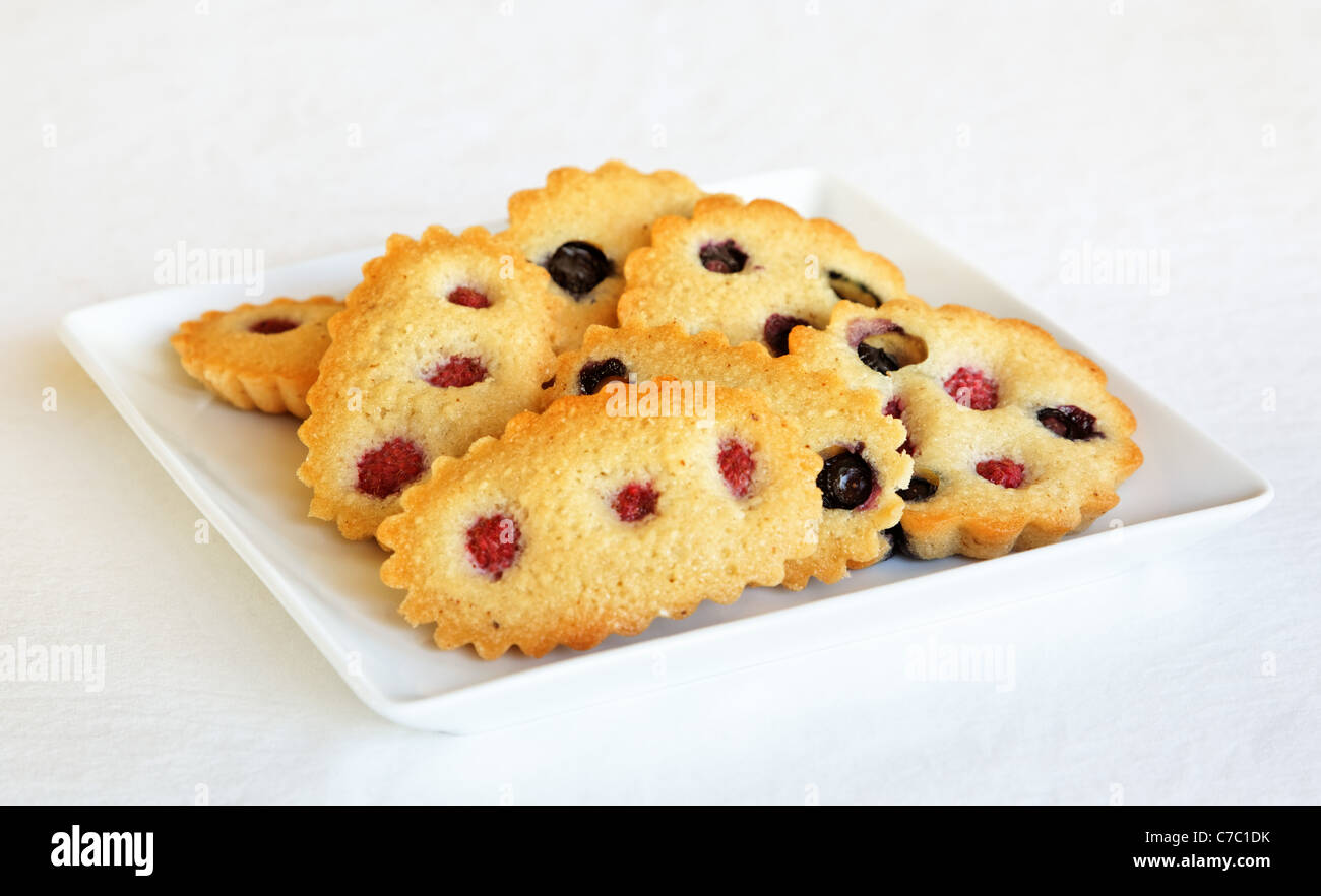 Raspberry and blueberry financier on white plate, by pastry chef Laurie Pfalzer, Pastry Craft - Stock Image