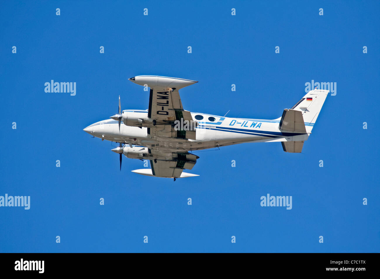A Cessna 340 twin engine aircraft flying low against a great blue sky - Stock Image