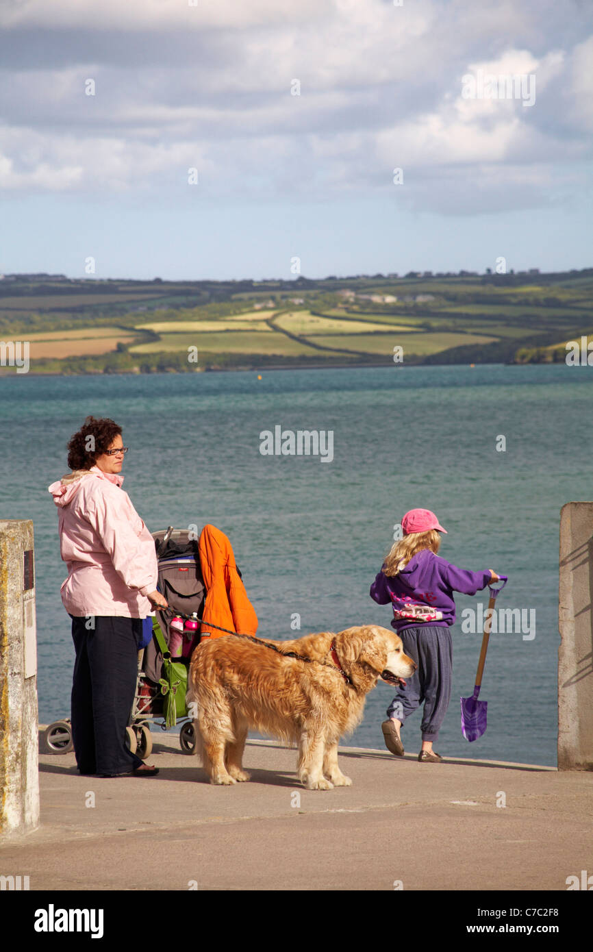 Mother and daughter with dog by waterside at Padstow with Rock in the distance in May - Stock Image