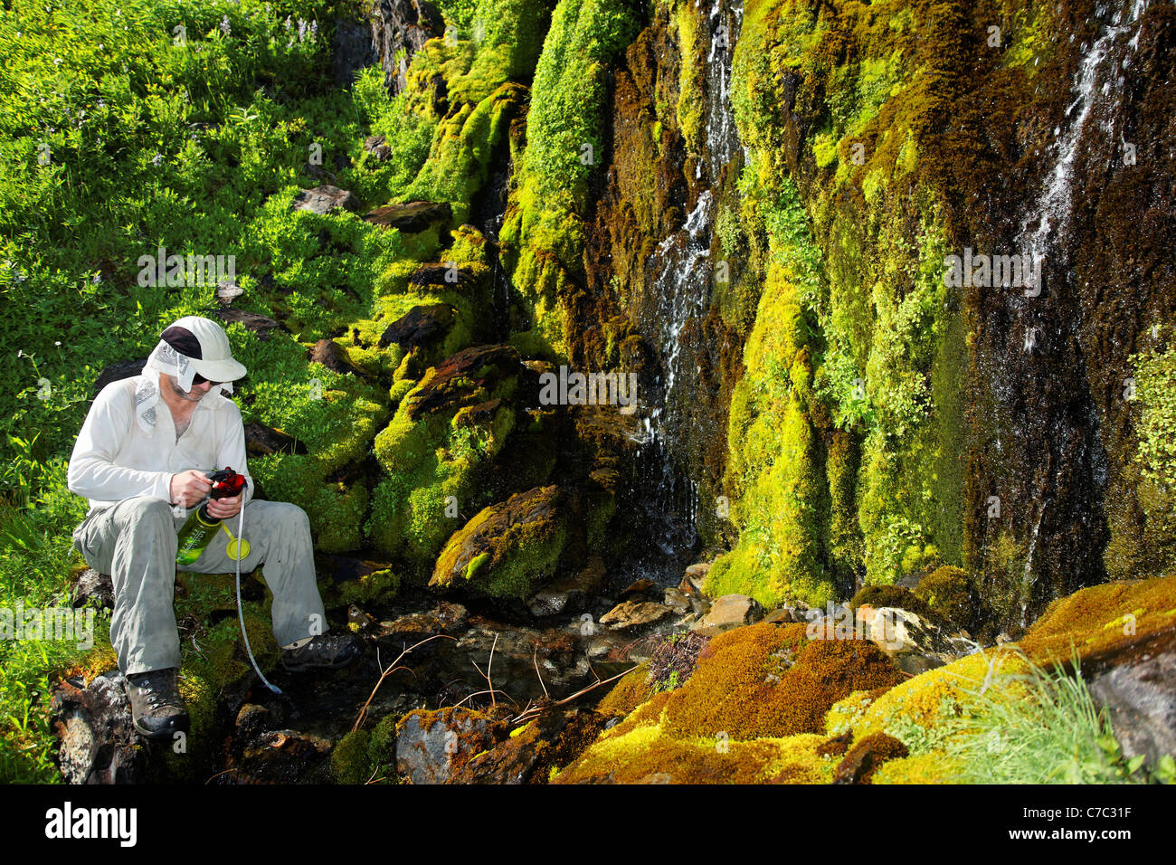 Hiker on Bailey Range Traverse pumping water from waterfall, Olympic Mountains, Olympic National Park, Washington - Stock Image