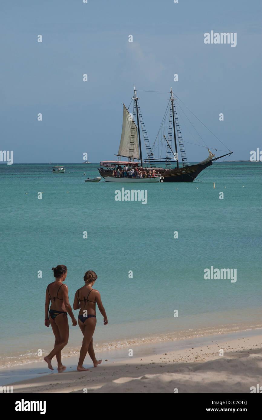Jolly Pirates sailing boat in Caribbean sea with two bikini dressed women walking on beach, palm beach, Aruba - Stock Image