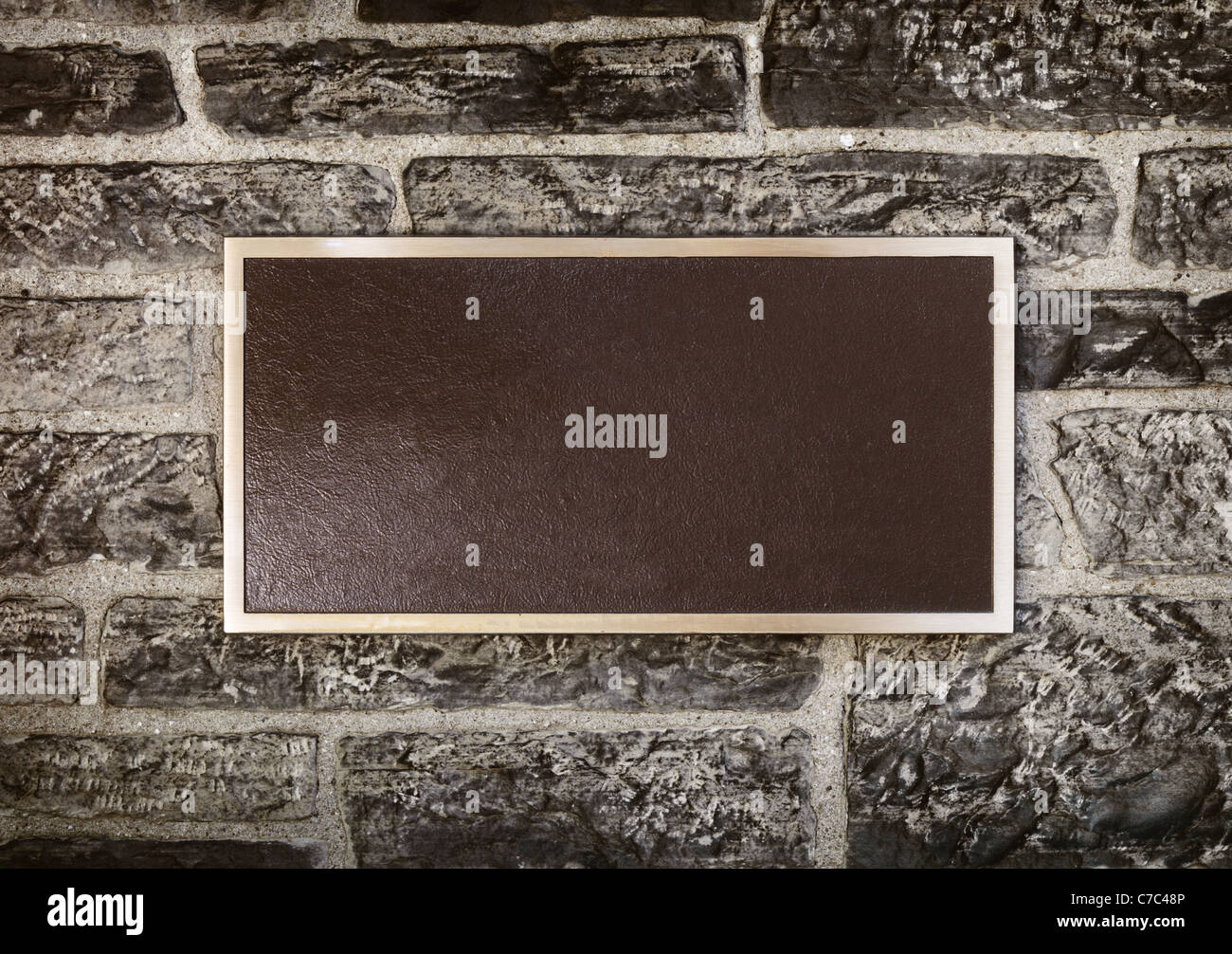 Blank sign in shiny metal frame on a stone wall - Stock Image