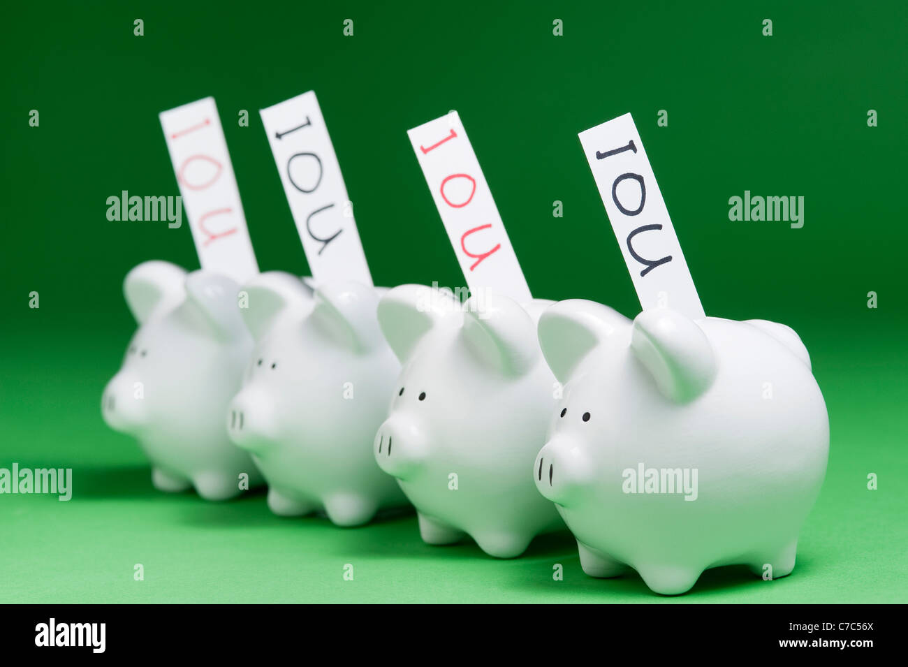 Group of piggy banks with IOU's coming out of coin slots Stock Photo