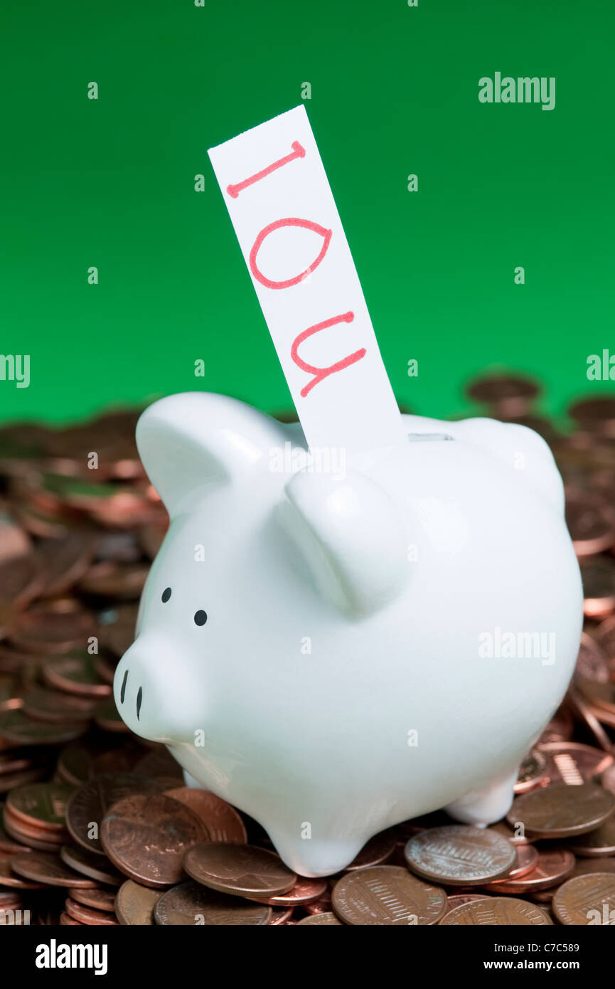 Piggy bank on a pile of pennies with an IOU coming out of the coin slot - Stock Image