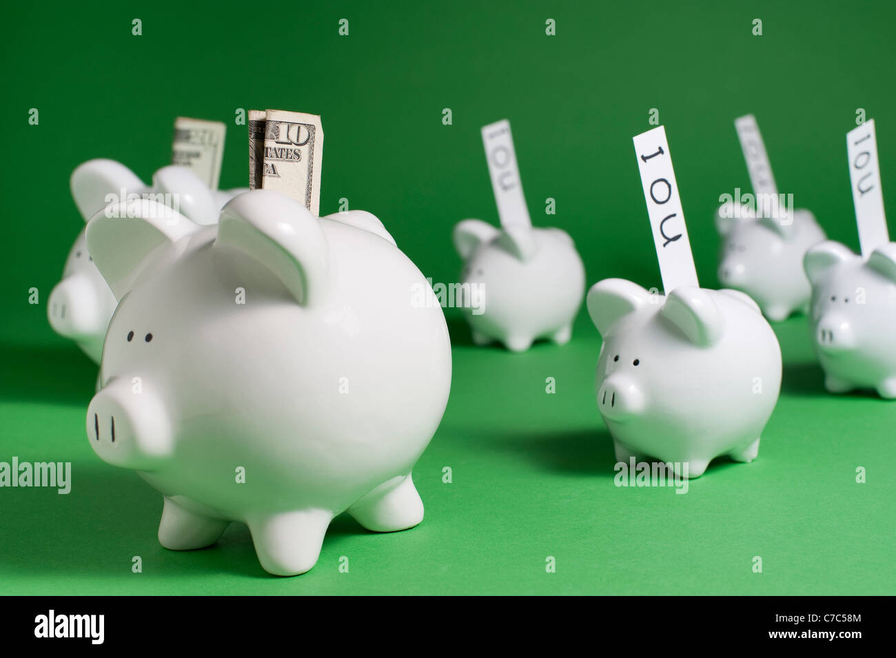 Group of pigs with money and IOU's coming out of coin slots - Stock Image