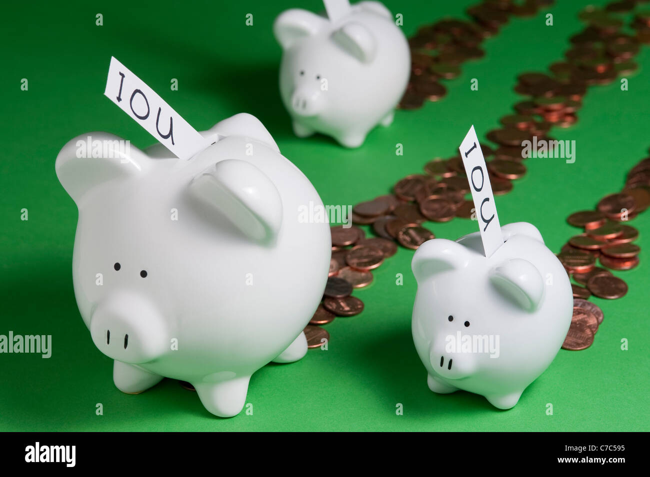 Piggy Bank's with IOU's coming out of coin slots and money coming out of piggy banks Stock Photo
