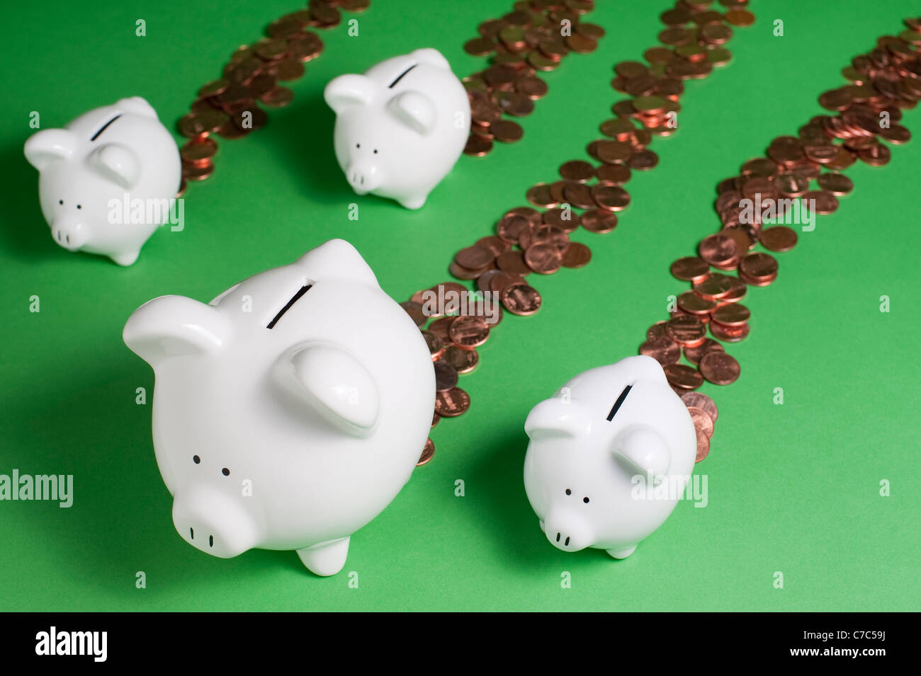 Group of Piggy Banks leaking pennies out back end losing money and savings Stock Photo