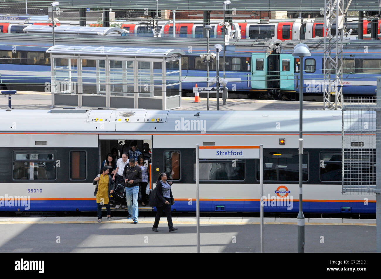 Public transport view from above looking down on Stratford London railway station commuters arriving at platform - Stock Image
