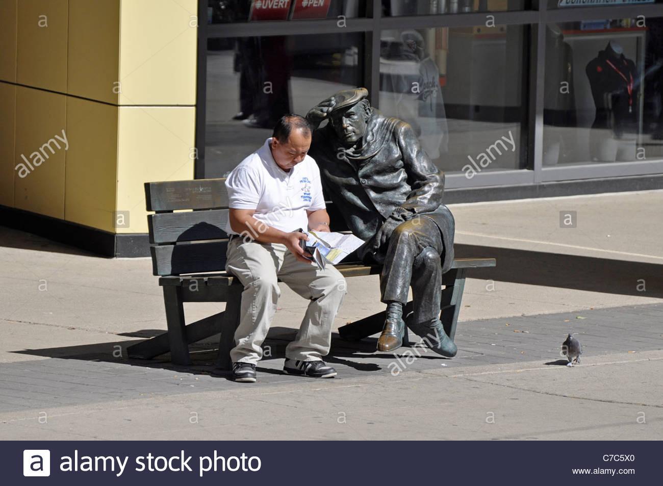 Man sitting on bench beside Glenn Gould Statue outside Glenn Gould Studio, Toronto, Canada - Stock Image