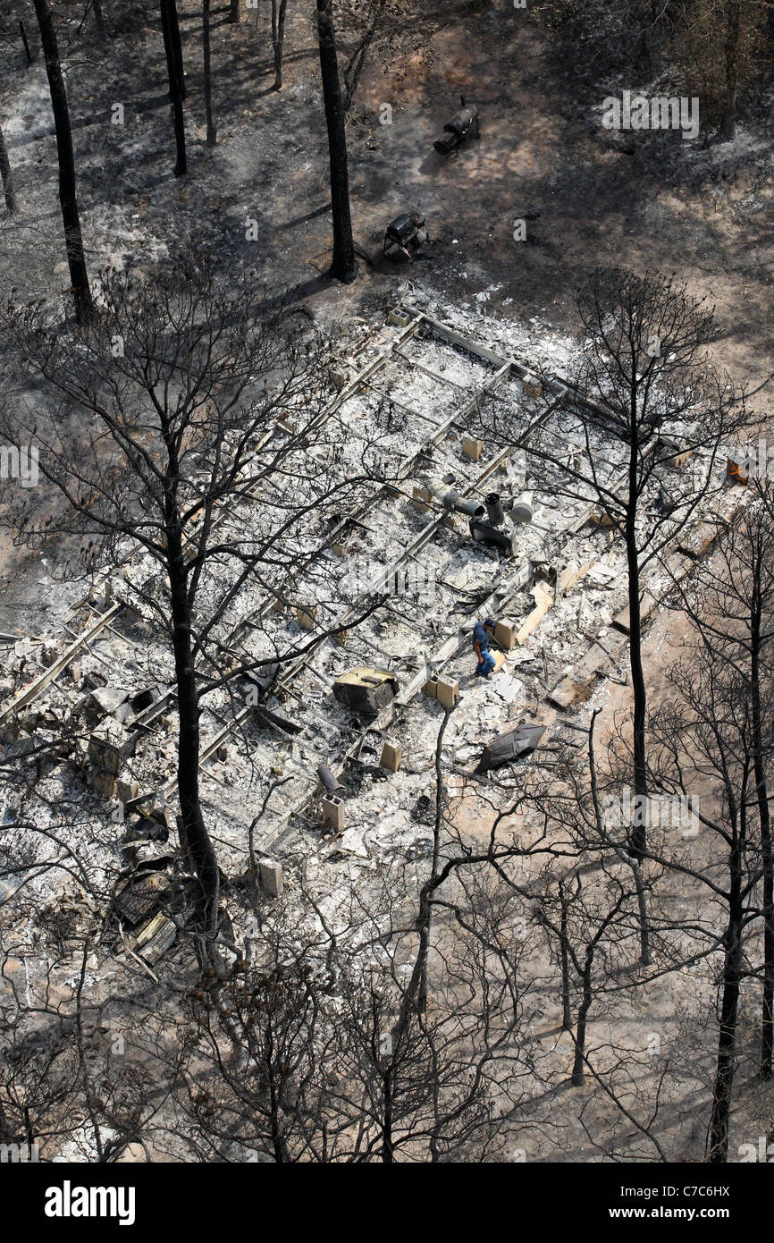 Aerial of wildfire damage in Bastrop County, TX shows foundation of burned-out home in heavily wooded residential - Stock Image