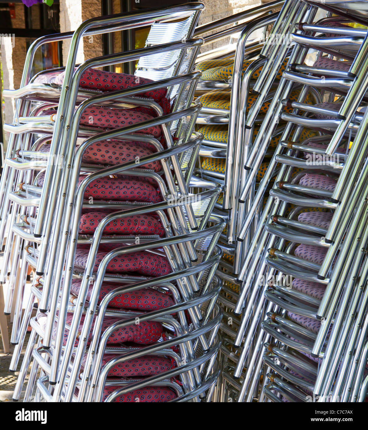 Three stacks of red, violet, and yellow seat stainless steel chairs nex to a restaurant Stock Photo