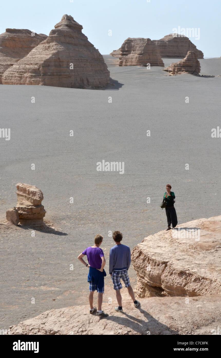 Tourists pose for a snapshot at the Yadan landforms, Gansu province, China - Stock Image