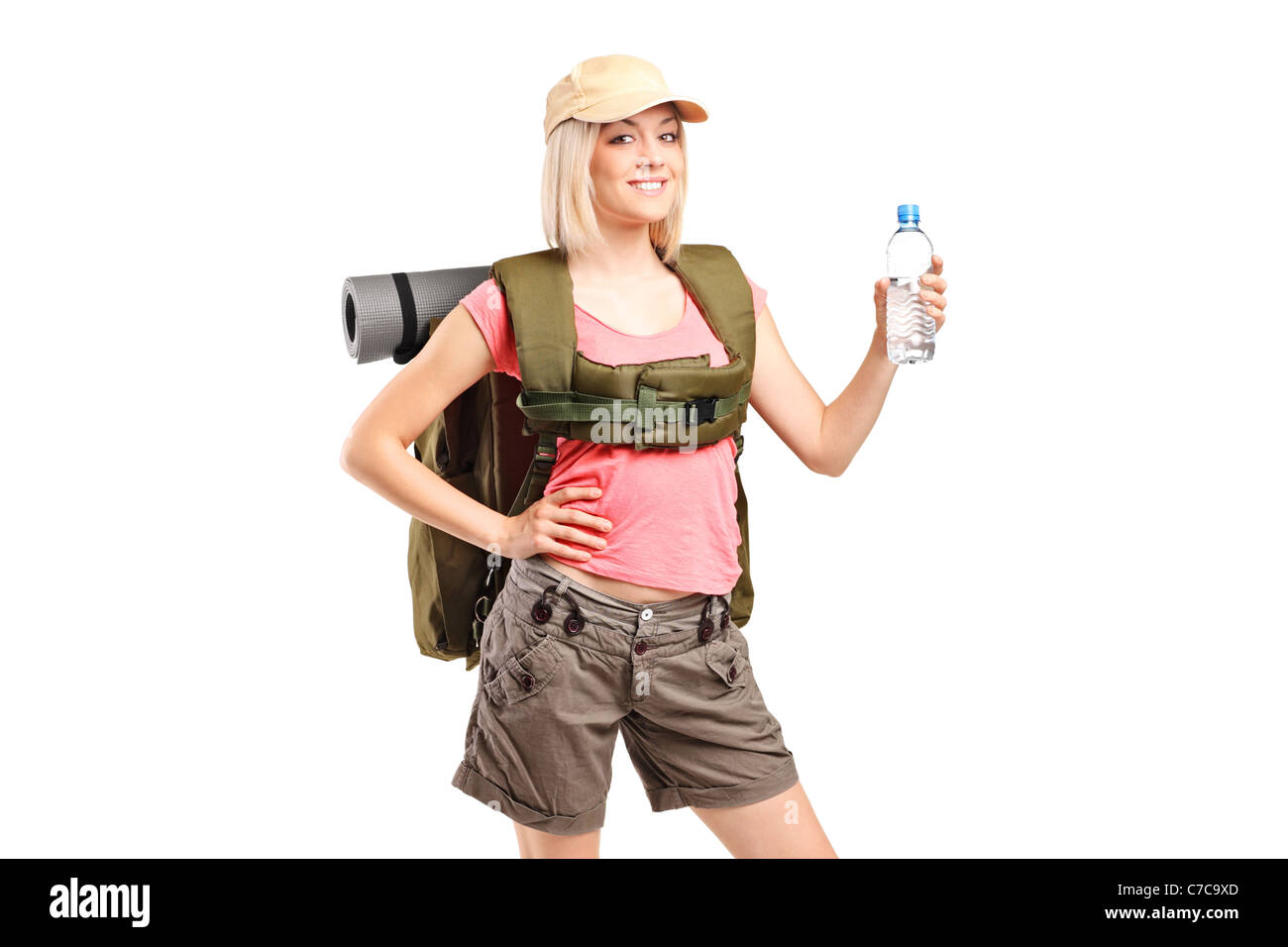 A woman hiker with backpack holding a bottle of water - Stock Image