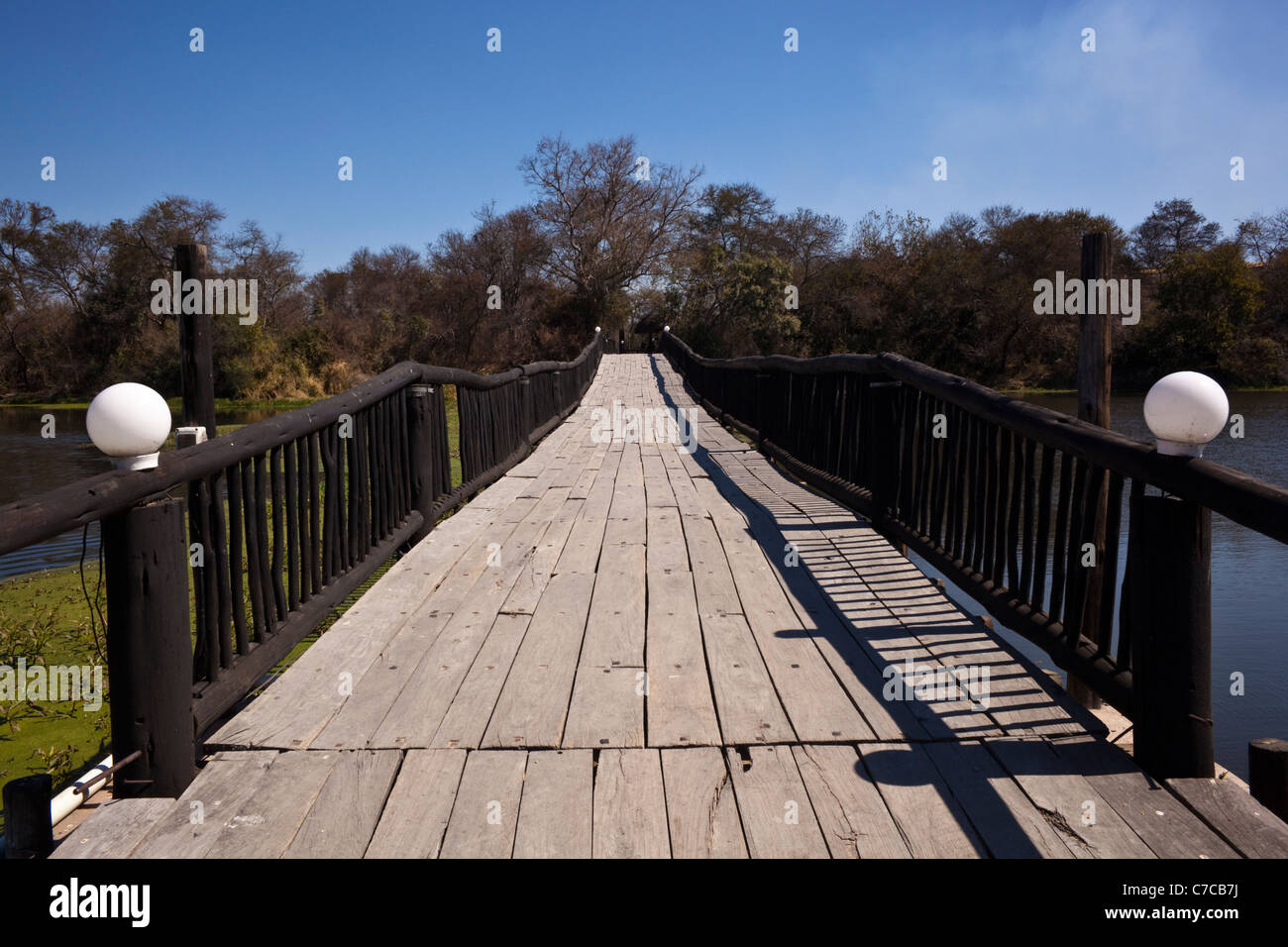 A Wooden Bridge Over A River With Trees And Blue Sky In The